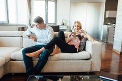 Eifersüchtige Frau, die ihren Partner plaudert am Telefon betrachtet lizenzfreies stockbild