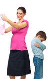 Eifersüchtiges Kind auf seiner schwangeren Mutter Stockfotografie