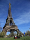 Eiffel Tower. Paris,France- April 1st, 2012: A young student studying in the grass at the base of the famous Eiffel Tower in a spring morning Royalty Free Stock Photos