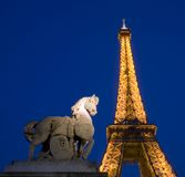 Eiffel Tower. At night with a horse statue nearby Royalty Free Stock Photo