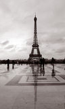 Eiffel tower. Reflection with people passing by Stock Images