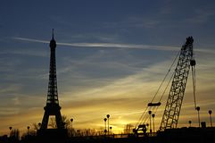 Eiffel Tower. And chrane tower are silhouetted against a Paris sunset Royalty Free Stock Image