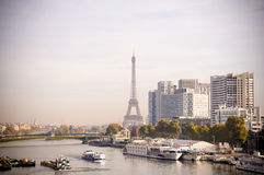 Eiffel tower behind the river of paris with boats. During fall Royalty Free Stock Images