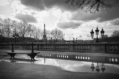 Eiffel Tower and a bench in Tuileries Garden in Paris, France. Black and white image of a bench in the public park close to the Louvres and the Concorde Square stock photo
