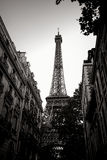 Eiffel Tower in Black and White in Paris France. The Eiffel Tower landmark at the end of a quiet residential neighborhood Parisian street with old French city Royalty Free Stock Image