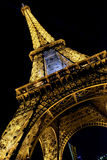 Eiffel Tower brightly illuminated at dusk in Paris. Royalty Free Stock Photography