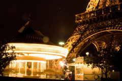 Eiffel Tower and carousel. A spinning carousel next to the Eiffel Tower in Paris at night Royalty Free Stock Images