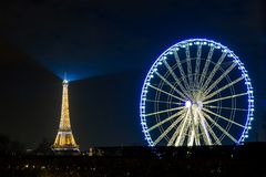 The Eiffel Tower and the ferris wheel at night in Paris, France stock image
