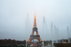 Eiffel Tower and fountains in evening fog. Stock Images