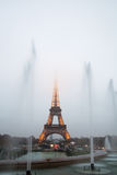 Eiffel Tower and fountains in evening fog. Royalty Free Stock Images