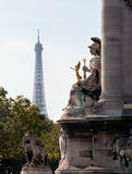 Eiffel tower framed by statue on Pont Alexandre. Statue on Pont Alexandre frames a distant hazy shot of the Eiffel Tower royalty free stock photos