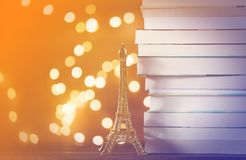 Eiffel tower gift and pile of books with Fairy lights. On background stock photo