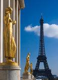 Eiffel Tower Gilded Statues. Eiffel Tower in Paris, France with golden statues of the Palais du Chaillot in the foreground Stock Photo