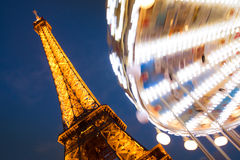 The Eiffel Tower and its Carousel. The Eiffel Tower Carousel spins in motion in the foreground of Le Tour Eiffel.  The Eiffel Tower is France's most visited Stock Images