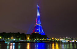 The Eiffel tower lit up in color of French flag, Paris, France. Stock Photos