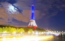 The Eiffel tower lit up with colors of French national flag. Stock Images