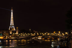 Eiffel Tower lit up at night. Paris, France June 27 2013: Eiffel Tower lit up at night with River Seine and city lights Royalty Free Stock Photos