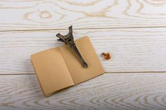 Eiffel tower miniature and a potion bottle on a brown notebook o. N a wooden background royalty free stock image