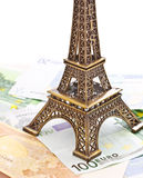 Eiffel tower model and Euro banknotes. Bronze Eiffel tower model placed on Euro banknotes on white background Royalty Free Stock Photos