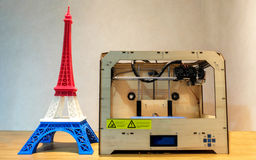 Eiffel Tower Model with Red White Blue Stripe printed by 3D Printer with 3D Printer on Wooden Table Stock Photos
