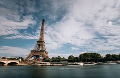 Eiffel tower near the Seine river, Paris symbol and iconic landmark in France, on a bright sunny day. Famous touristic. Places and romantic travel destinations Royalty Free Stock Image