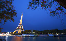 Eiffel Tower by night. PARIS - October 25: Eiffel Tower light show at dusk with Seine river on foreground on October 25, 2011 in Paris, France. Eiffel Tower is Royalty Free Stock Photography