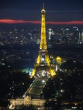 The Eiffel Tower at Night. The Eiffel Tower amidst the lights of Paris as the last rays of evening sun fade through the clouds. Ecole Militaire, Champ de Mars Stock Photos