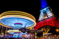 Eiffel tower at night. And carusel. Colors of the french flag after Paris attacks in 2015 13th of November stock image