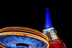 Eiffel tower at night. And carusel. Colors of the french flag after Paris attacks in 2015 13th of November royalty free stock image