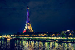 Eiffel tower at night. The river. Colors of the french flag after Paris attacks in 2015 13th of November royalty free stock image