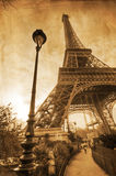 Eiffel tower with old paper texture. Eiffel Tower and an old street lamp in the park, overlaid with an old paper texture for a vintage look Stock Images