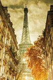 Eiffel Tower on old paper texture. Vintage style picture of a street view with the Eiffel Tower at the end, overlaid with an old folded paper Stock Image