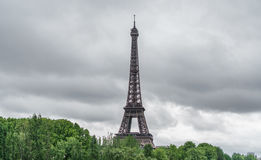 The Eiffel Tower over trees, stormy clouds Royalty Free Stock Photos