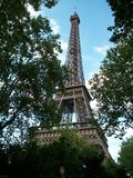 Eiffel Tower in Paris, France. The Eiffel Tower can be seen through an opening in the trees. The picture is taken from the lower section of the tower, looking up Royalty Free Stock Photo