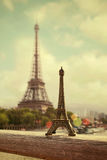 Eiffel Tower, Paris, France. Eiffel Tower souvenir in front of real tower. Retro filter effect. Royalty Free Stock Photo