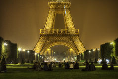 Eiffel Tower, Paris by night. Silhouettes hanging out on the lawn in front of the illuminated Eiffel Tower on a September night Royalty Free Stock Photos