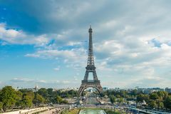 Eiffel tower, Paris symbol and iconic landmark in France, on a sunny day with clouds in the sky. Famous touristic places Stock Photos