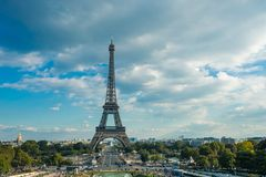 Eiffel tower, Paris symbol and iconic landmark in France, on a sunny day with clouds in the sky. Famous touristic places. And romantic travel destinations in Stock Photo
