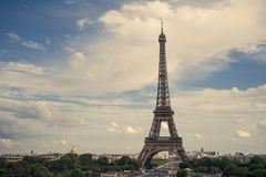 Eiffel tower, Paris symbol and iconic landmark in France, on a sunny day with clouds in the sky. Famous touristic places. And romantic travel destinations in Royalty Free Stock Photos