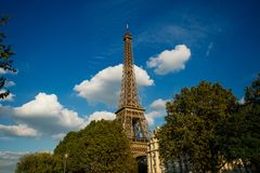 Eiffel tower, Paris symbol and iconic landmark in France, on a sunny day with clouds in the sky. Famous touristic places. And romantic travel destinations in Stock Images