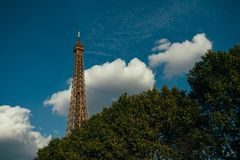 Eiffel tower, Paris symbol and iconic landmark in France, on a sunny day with clouds in the sky. Famous touristic places. And romantic travel destinations in Royalty Free Stock Photography