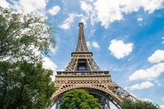 Eiffel tower, Paris symbol and iconic landmark in France, on a sunny day with clouds in the sky. Famous touristic places Royalty Free Stock Photo