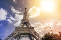 Eiffel tower, Paris symbol and iconic landmark in France, on a sunny day with sunbeams in the sky. Famous touristic Royalty Free Stock Photos