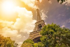 Eiffel tower, Paris symbol and iconic landmark in France, on a sunny day with sunbeams in the sky. Famous touristic Royalty Free Stock Image