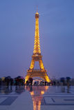Eiffel tower in Paris with tourists at dusk Stock Photos