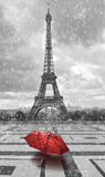 Eiffel tower in the rain. Black and white photo with red element. Eiffel tower in the rain with red umbrella. Black and white photo with red element Stock Image