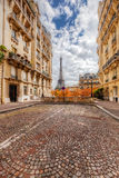 Eiffel Tower seen from the street in Paris, France. Cobblestone pavement royalty free stock photos