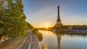 Eiffel Tower and the Seine river at Sunrise timelapse, Paris, France. Morning view from Bir-Hakeim bridge with reflections on water and traffic on the street stock footage