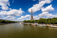Eiffel Tower and Seine River with White Clouds in Background Stock Image