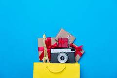Eiffel tower shaped toy, camera and gifts in shopping bag  on th Stock Photography